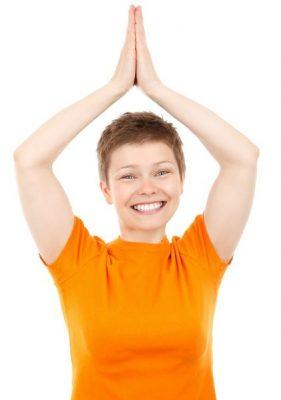 Vrouw legt handpalmen boven haar hoofd tegen elkaar